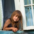 Little girl looks out the window rural house. — Stock fotografie