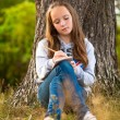 Stock Photo: Teen-girl writing in notebook while sitting in park