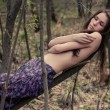 Stock Photo: Young womtopless hiding her naked chests under her arms in forest