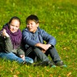 Stock Photo: Teenage couple sit in autumn park