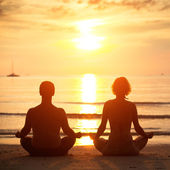 Yoga practice: a young couple sitting on the beach of the sea in the lotus position at sunset. — Stok fotoğraf
