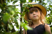 Little lovely girl posing in a straw hat in the park — Stock Photo
