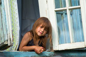 Little girl looks out the window rural house. — Stock Photo