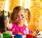 Kleines kind, zeichnen malen mit farbe des gesichts. — Stockfoto