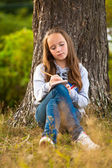 Teen-girl writing in a notebook while sitting in the park — Stock Photo