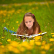 A girl (11 years old) reads a book in the meadow. — Stock Photo