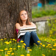 Tired teen girl with books in the village — Stock fotografie