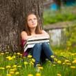 Tired teen girl with books in the village — Stockfoto