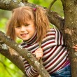 Lovely little girl posing sitting on a tree in the garden — Zdjęcie stockowe
