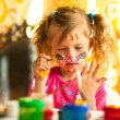 Child drawing paint with paint of face — Stockfoto