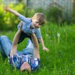 Stock Photo: Father playing with his small son in the grass