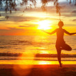 Young woman practicing yoga by the sea at sunset — Stockfoto