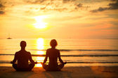 Young couple practicing yoga on the beach at sunset. — Stock Photo