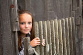Beautiful teen-girl standing near vintage rural fence. — Stock Photo