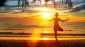 Young woman practicing yoga by the sea at sunset — Stock Photo