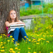 Tired teen-girl in the park with books — Stok fotoğraf