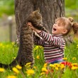 Kid playing with a cat — Stockfoto