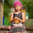 Stock Photo: Little five-year girl on the porch of a village house.