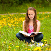 Teen girl reading a book in a field — Stock Photo