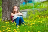 Tired teen-girl in the park with books — Stock Photo