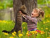Kind spielt mit einer katze — Stockfoto