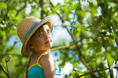 Little lovely girl posing in a straw hat in the park. — Stock Photo