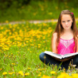 Girl sits on a grass and reads the book — Stock Photo