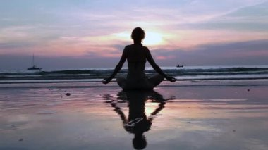 Silhouette young woman practicing yoga on the beach at sunset. — Stock Video