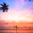 Silhouette young woman in a jump on the sea beach at sunset. — Stock Photo #33095145