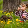 Stock Photo: Lovely little girl and cat, blowing soap bubbles