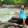 Teengirl in a blue dress in the rocks of the coast. — Stock Photo