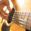 Female hand playing on acoustic guitar. Close-up. — Stock Photo