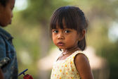 An unidentified poor child poses for tourists near Angkor Wat — Stockfoto