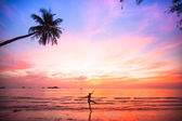 Silhouette young woman in a jump on the sea beach at sunset. — Stock Photo