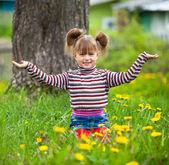 Krásné pětileté holčičky sedící v trávě. — Stock fotografie