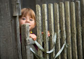 Beautiful child standing near vintage rural fence. — Stock Photo