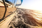 Yacht sailing towards the sunset. — Stock Photo
