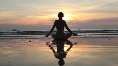 Silhouette woman practicing yoga on the beach at sunset. — Stock Video