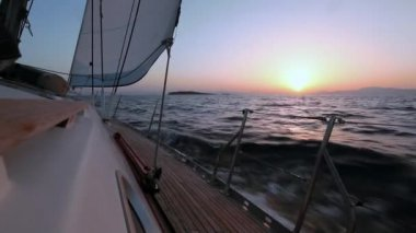 Sailing boat in the wind through the waves during sunset shot in full HD — Stock Video