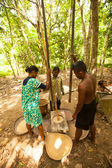 Unidentified people Orang Asli thresh rice to remove chaff in Berdut, Malaysia — Stock Photo