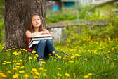 Teengirl in the park with books. — Stock Photo
