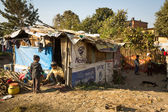 Unidentified poor people near their houses at slums — Stock Photo