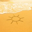 Sun drawn in the sand of a beach, soft surf wave. — Stock Photo #38719395