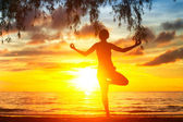 Young woman silhouette practicing yoga on the beach at sunset. — Stock Photo