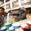 Unidentified man sell cement for donations for repairs near stupa Boudhanath — Stock Photo