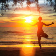 Silhouette young woman practicing yoga on the beach at sunset. — Stock Photo #38728791