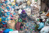 Unidentified people from poorer areas working in sorting of plastic on the dump — Stock Photo