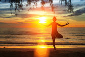 Silhouette young woman practicing yoga on the beach at sunset. — Foto de Stock