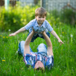 Father and son playing in the grass. — ストック写真