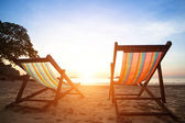 Pair of beach loungers on the deserted coast sea at sunrise — Stock Photo